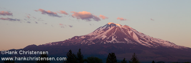 The setting sun casts Mount Shasta in shades of red and purple, Weed, California