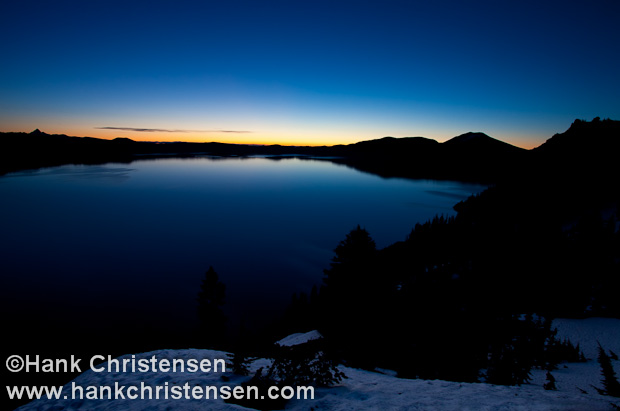 Light from the rising sun turns a blue sky orange and silhouettes the distant rim, Crater Lake National Park, Oregon