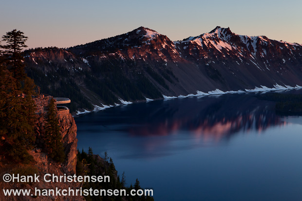 The light of sunrise casts the overlook and the surrounding rim of Crater Lake in a warm glow, Crater Lake National Park, Oregon