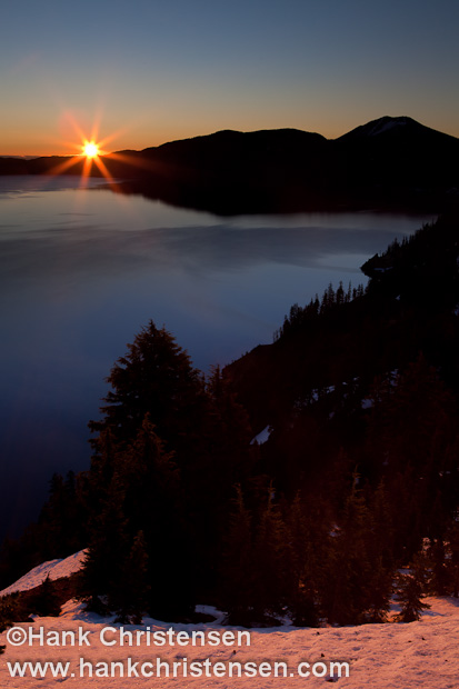 The sun peaks over the crater\'s rim, casting Crater Lake in the warm glow of sunrise, Crater Lake National Park, Oregon