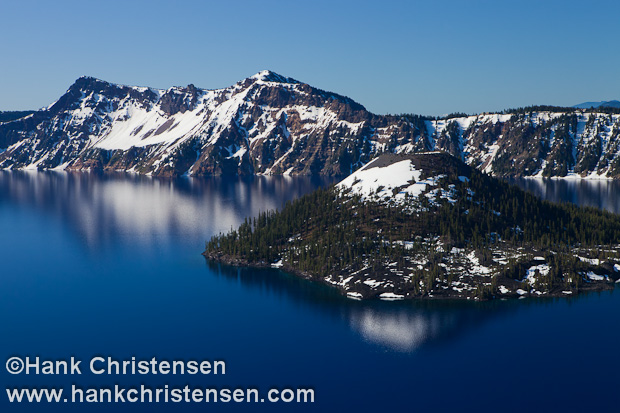 Snow-capped Wizard Island sits in the deep blue waters of Crater Lake