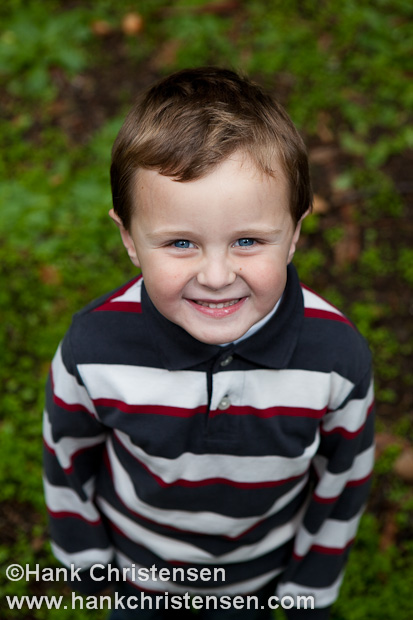 A portrait of a boy smiling from above.  Green moss background.