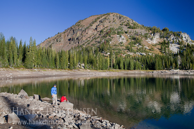Two backpackers pump water from Crater Lake in the early morning as the surrounding hillside reflects off the lake's surface, Eagle Cap Wilderness, Oregon