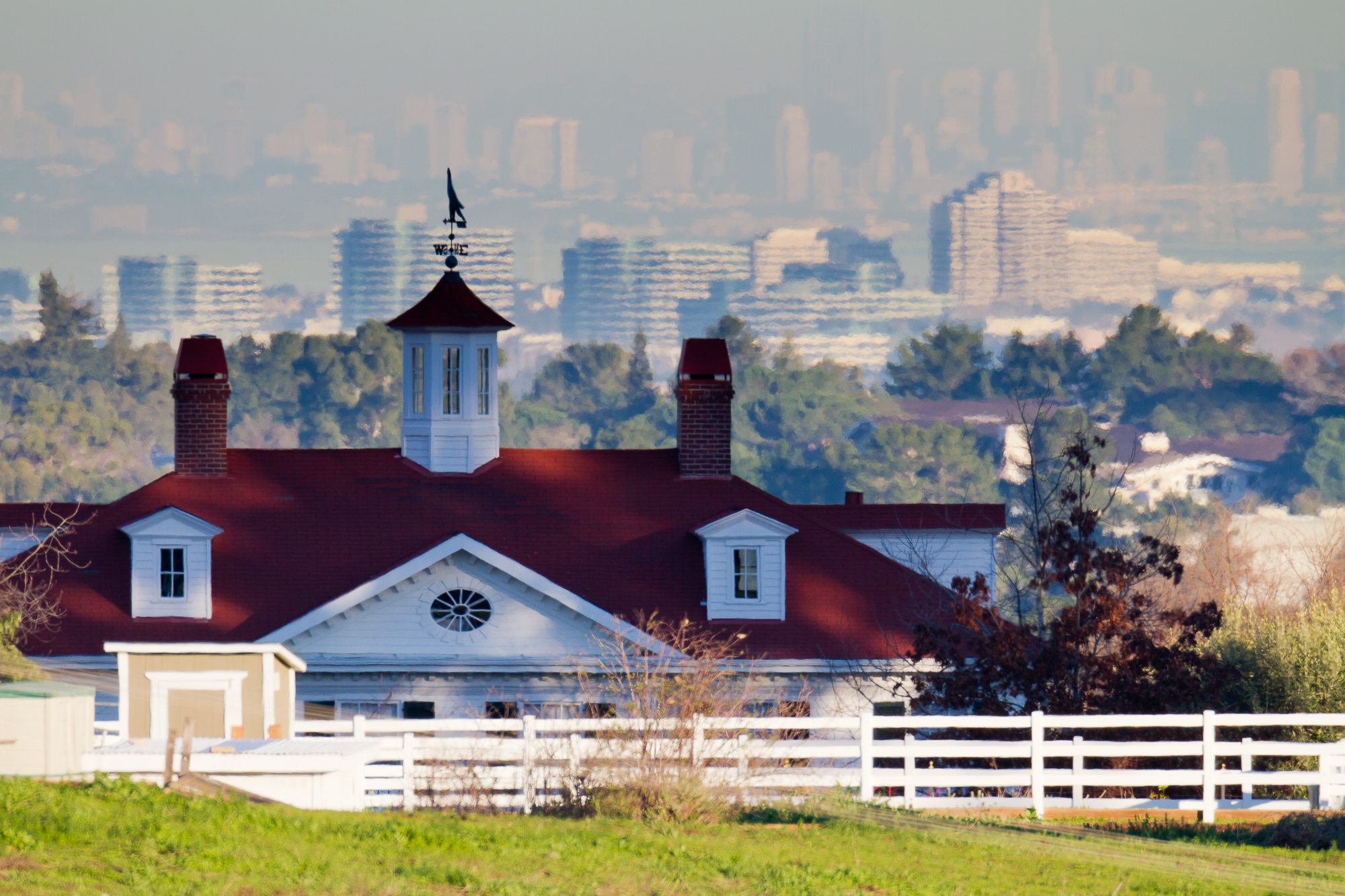 A view of a Palo Alto home includes the city of San Mateo in the midground and San Francisco in the background.  The view is compressed using a long telephoto lens.