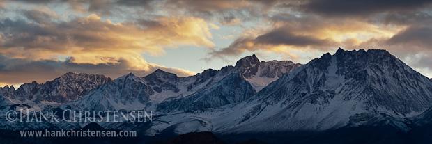 The sun lights stormy clouds as sets behind the eastern Sierra range, north of Bishop