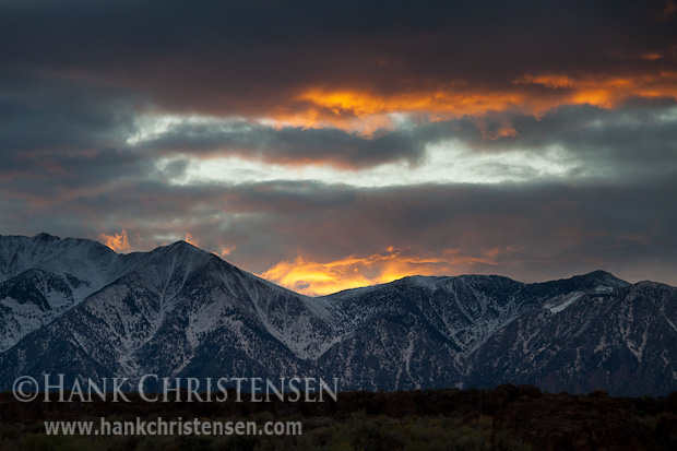 The sun plays dramatically across storm clouds as it sets behind the eastern Sierra range