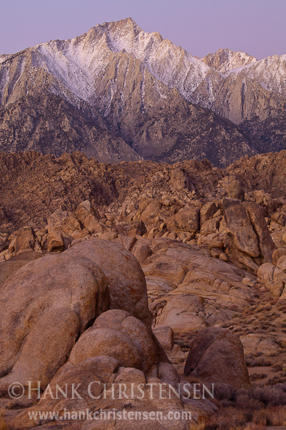 Dawn begins to light Mt. Langley and the wild rock formations of the Alabama Hills