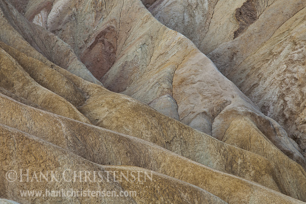 Muted light plays across the ridges of rock at Zabriskie Point, Death Valley National Park