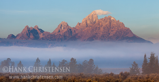 A fog bank moves in front of the Grand Tetons as the rising sun illuminates the sheer peaks, Grand Teton National Park