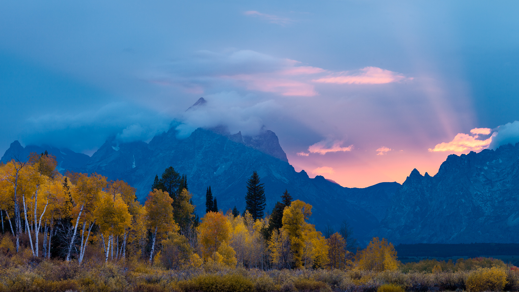 Dramatic light bursts from behind the Tetons at sunset.  Thick smoke and haze from nearby forest fires create God beams as the sun drops behind the horizon, Grand Teton National Park