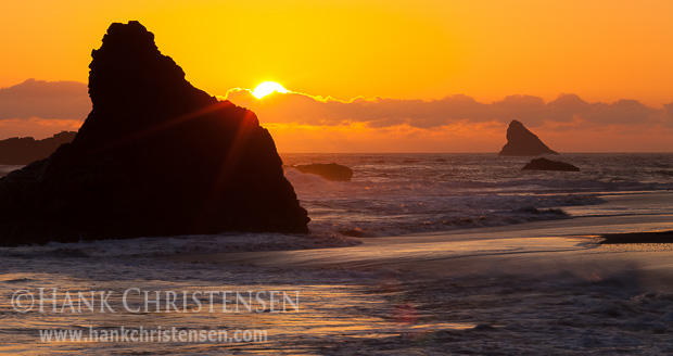 The sun sets behind offshore sea stacks, Harris Beach State Park