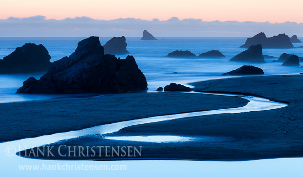 The sun sets behind a bank of offshore clouds, silhouetting the sea stacks at Harris State Beach, Oregon
