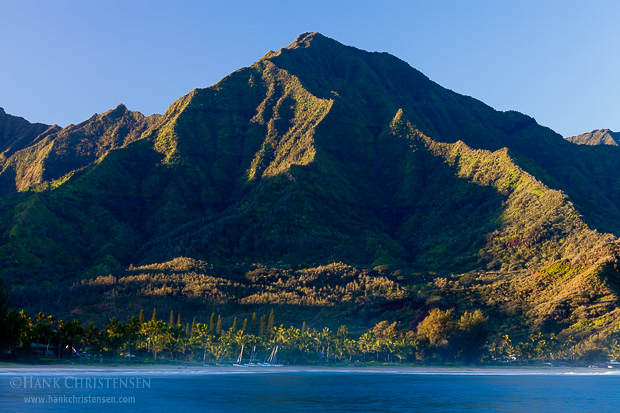 Green mountains covered with waterfalls rise from the shores of Hanalei Bay, catching the first rays of sunlight, Kauaii