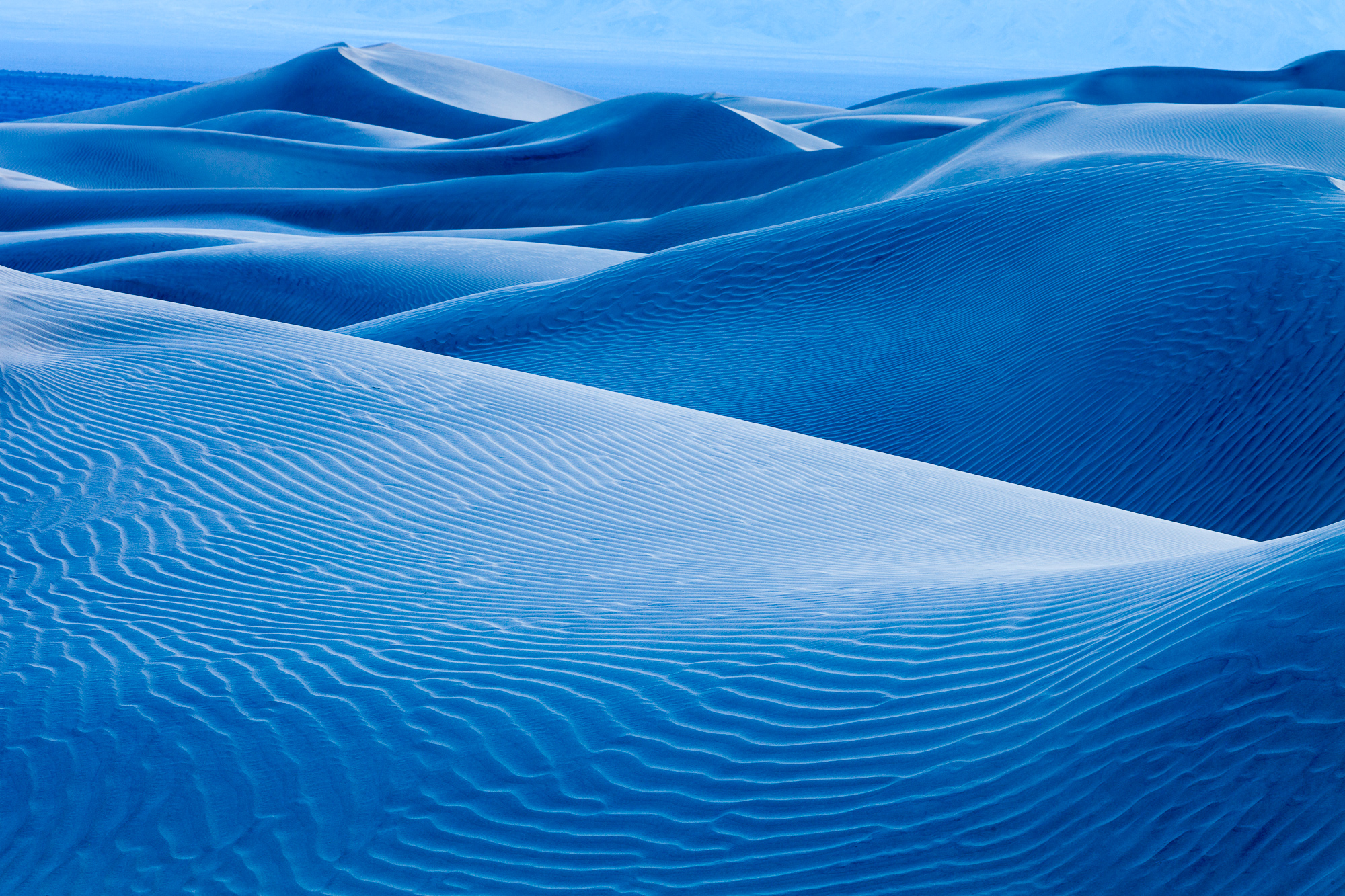 Blue shadows of twilight dance over the dunes of Death Valley National Park
