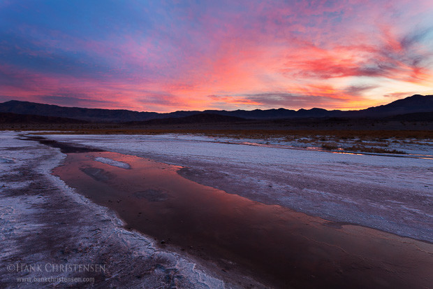 Dawn breaks over a basin of rivulets winding through salt flats, Death Valley National Park