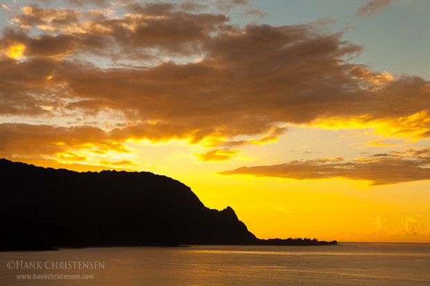 The sun sets behind the northern cliffs of the Napali coast, Hanalei Bay, Kauai