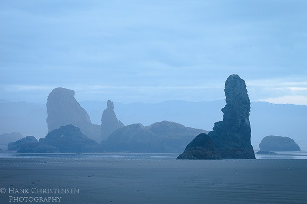 The sun rises on a blue, dreary day along Bandon Beach Oregon