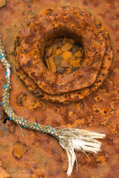 A frayed rope lies against dark rusted metal in a boat repair yard