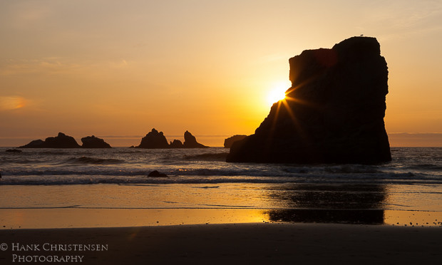 The setting sun at Bandon Oregon turns the sky an orange pink and turns the sea stacks into silhouettes.