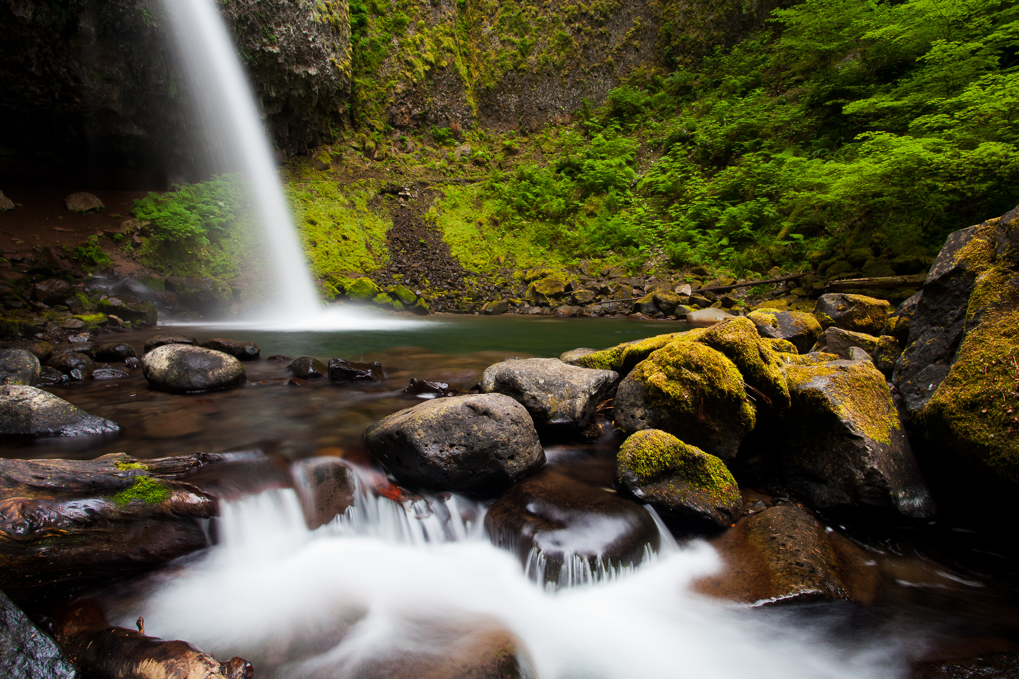 Ponytail Falls shoots outward from a cleft in a rock cliff, and cascades over large stones below, Columbia River Gorge, Oregon